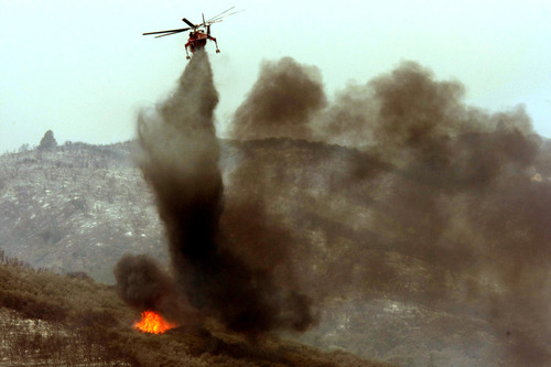 A helicopter puts out a hot spot on the Powerhouse fire at Elizabeth Lake on Sunday, June 2, 2013. Erratic winds fanned a blaze in the Angeles National Forest to nearly 41 square miles early Sunday, after fast-moving flames triggered the evacuation of nearly 1,000 homes in Lake Hughes and Lake Elizabeth, officials said. (AP Photo/Los Angeles Times, Genaro Molina)  NO FORNS; NO SALES; MAGS OUT; ORANGE COUNTY REGISTER OUT; LOS ANGELES DAILY NEWS OUT; VENTURA COUNTY STAR OUT; INLAND VALLEY DAILY BULLETIN OUT; MANDATORY CREDIT, TV OUT