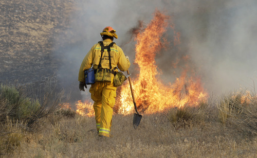 A Los Angeles County firefighter approaches a fire along a road in what has been called the Powerhouse fire in Lake Hughes, Calif., early Sunday, June 2, 2013. Erratic wind fanned the blaze in the Angeles National Forest to nearly 41 square miles early Sunday, after fast-moving flames triggered the evacuation of nearly 1,000 homes in Lake Hughes and Lake Elizabeth, officials said. (AP Photo/Reed Saxon)