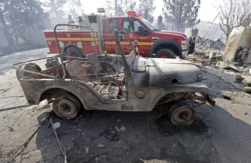 A burned-out Jeep is parked next to a Los Angeles County Fire Department rig at one of at least five structures destroyed or severely damaged in what has been called the Powerhouse fire in Lake Hughes, Calif., early Sunday, June 2, 2013. Erratic wind fanned the blaze in the Angeles National Forest to nearly 41 square miles early Sunday, after fast-moving flames triggered the evacuation of nearly 1,000 homes in Lake Hughes and Lake Elizabeth, officials said. (AP Photo/Reed Saxon)