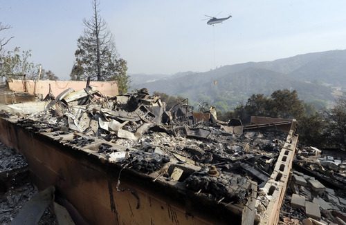 A firefighting helicopter carries a large water bucket behind a home that has been destroyed, one of at least five structures destroyed or severely damaged in what has been called the Powerhouse fire in Lake Hughes, Calif., early Sunday, June 2, 2013. Erratic wind fanned the blaze in the Angeles National Forest to nearly 41 square miles early Sunday, after fast-moving flames triggered the evacuation of nearly 1,000 homes in Lake Hughes and Lake Elizabeth, officials said. (AP Photo/Reed Saxon)