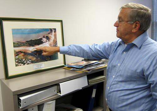 "This photo taken May 3, 2013 shows Hank Mann, 72, an engineer at Stanley Consultants, pointing at an image of a highway project he worked on, at the company's headquarters in Muscatine, Iowa. Mann is among the employees at Stanley who have participated in ""phased retirement,"" in which a worker can cut back their hours in the months or years before their formal retirement, and continue to work part-time after. Employers around the country offer phased retirement, giving older workers a chance to transition more slowly to their post-career life. (AP Photo/Matt Sedensky)"