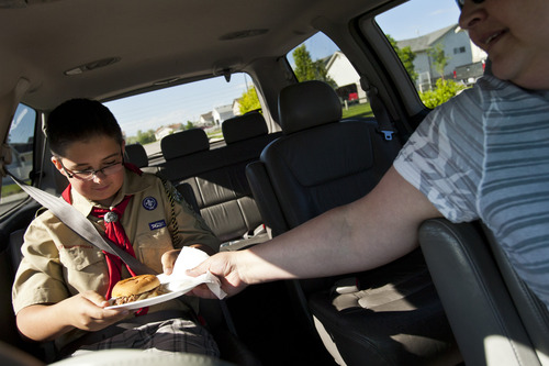 Chris Detrick  |  The Salt Lake Tribune Becky Fish gives her son Brady, 12, a sandwich as part of his dinner in their van after picking him up from his Scout meeting on their way to her daughters' choir concert in Magna on Thursday, May 30, 2013.