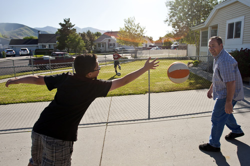 Chris Detrick  |  The Salt Lake Tribune Brady Fish and his dad, Derek, play basketball while his brother Danny, 9, practices soccer at their home in Magna on Thursday, May 30, 2013.
