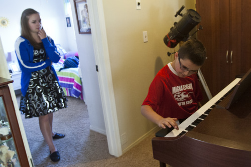 Chris Detrick  |  The Salt Lake Tribune Laurel Fish, 16, watches as her brother Danny, 9, practices the piano at their home in Magna on Thursday, May 30, 2013.