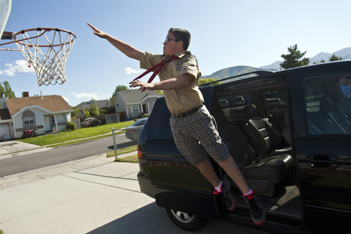 Chris Detrick  |  The Salt Lake Tribune Brady Fish leaps off of the van to dunk on the basketball hoop after his Scout meeting in Magna on Thursday, May 30, 2013.