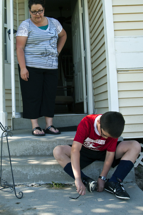 Chris Detrick     The Salt Lake Tribune Becky Fish watches as her son Danny, 9, puts on his soccer cleats at their home in Magna on Thursday, May 30, 2013.