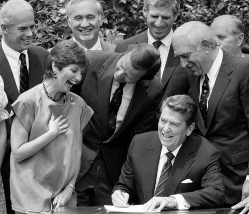 FILE - In this July 17, 1984 file photo, President Ronald Reagan, seated, signs legislation raising the national drinking age to 21 while New Jersey Democrat Sen. Frank Lautenberg, center right, New Jersey Gov. Thomas Kean, center and MADD founder Candy Lightner, center left, look on. Lautenberg, a multimillionaire New Jersey businessman who New Jersey Democrats recruited out of retirement in September 2002, has died at age 89. In addition, from left, back, are Rep. John Edward Porter, R-Ill.; Rep. Gene Snyder, R-Ky. and Sen. John Danforth, R-Mo. (AP Photo, File)