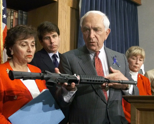 FILE - In this June 16, 1999 file photo, Sen. Frank Lautenberg, D-N.J., displays an AR-15 carbine at a news conference on Capitol Hill where he and other Democrats urged the House to pass his version of gun control legislation. Lautenberg, a longtime advocate of gun control, died Monday, June 3, 2013, at age 89. He returned to the Senate in April 2013 despite poor health for several votes on gun legislation favored by President Barack Obama. In the background are, from left to right: Rep. Nikta Lowey, D-N.Y.; Rep. Rod Blagojevich, D-Ill.; Rep. Carolyn McCarthy, D, N.Y. (AP Photo/Dennis Cook, File)