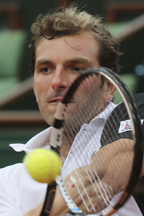 Julien Benneteau of France returns against Switzerland's Roger Federer in their third round match at the French Open tennis tournament, at Roland Garros stadium in Paris, Friday, May 31, 2013. (AP Photo/Michel Euler)