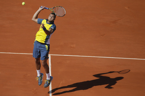 France's Jo-Wilfried Tsonga jumps to return against Switzerland's Roger Federer in their quarterfinal match at the French Open tennis tournament, at Roland Garros stadium in Paris, Tuesday June 4, 2013. (AP Photo/Michel Spingler)