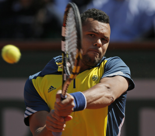France's Jo-Wilfried Tsonga returns against Switzerland's Roger Federer in their quarterfinal match at the French Open tennis tournament, at Roland Garros stadium in Paris, Tuesday June 4, 2013. (AP Photo/Petr David Josek)