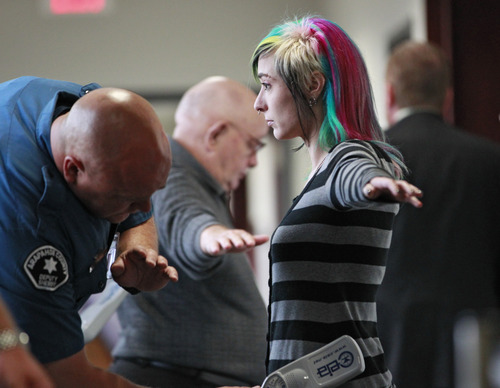 Sherriff's deputies search people before they enter district court for a hearing for Aurora theater shooting suspect James Holmes in Centennial, Colo., on Tuesday, June 4, 2013. Judge Carlos A. Samour Jr. accepted a plea of not guilty by reason of insanity from Holmes.  He also ruled that prosecutors can have access to a notebook Holmes sent to a psychiatrist before last summer's rampage. (AP Photo/Brennan Linsley)