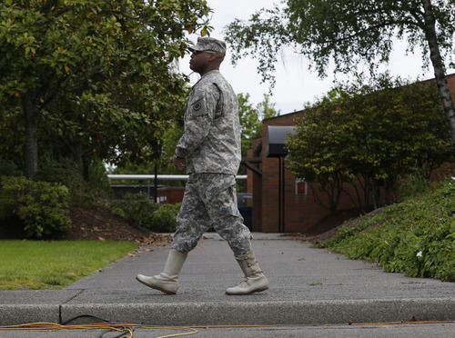 Lt. Col. Gary Dangerfield, a public affairs officer at Joint Base Lewis McChord, Wash., walks Wednesday, June 5, 2013, outside the building housing the military courtroom where U.S. Army Staff Sgt. Robert Bales was taking part in a plea hearing. Bales is accused of 16 counts of premeditated murder and six counts of attempted murder for a pre-dawn attack on two villages in Kandahar Province in Afghanistan in March, 2012. (AP Photo/Ted S. Warren)