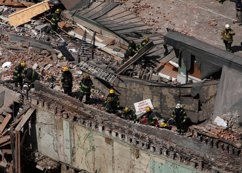 Rescue personnel search the scene of a building collapse in downtown Philadelphia Wednesday June 5, 2013.  A four-story building being demolished collapsed Wednesday on the edge of downtown, injuring 12 people and trapping two others, the fire commissioner said. Rescue crews were trying to extricate the two people who were trapped, city Fire Commissioner Lloyd Ayers said. The dozen people who were injured were taken to hospitals with minor injuries, he said. (AP Photo/Jacqueline Larma)