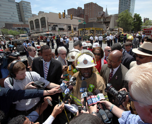 Philadelphia Fire Commissioner Lloyd Ayers addresses the media alongside Mayor Michael Nutter, left, at the scene of a building collapse in downtown Philadelphia Wednesday June 5, 2013.  A four-story building being demolished collapsed Wednesday on the edge of downtown, injuring 12 people and trapping two others, the fire commissioner said.  (AP Photo/Jacqueline Larma)