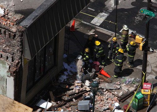 Rescue personnel removed debris from the area of a collapsed building in downtown Philadelphia Wednesday June 5, 2013.  A four-story building being demolished collapsed Wednesday on the edge of downtown, injuring 12 people and trapping two others, the fire commissioner said.   (AP Photo/Jacqueline Larma)