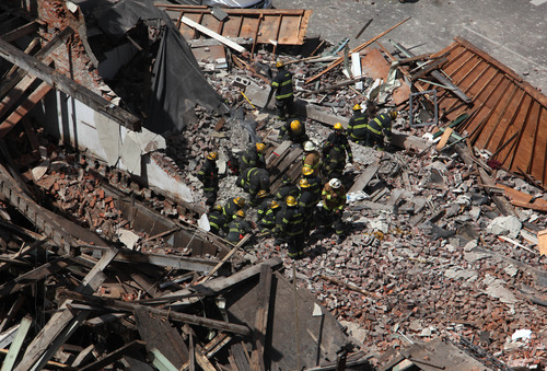 Rescue personnel work at the scene of a building collapse in  downtown Philadelphia Wednesday June 5, 2013.  A four-story building being demolished collapsed Wednesday on the edge of downtown, injuring 12 people and trapping two others, the fire commissioner said. Rescue crews were trying to extricate the two people who were trapped, city Fire Commissioner Lloyd Ayers said. The dozen people who were injured were taken to hospitals with minor injuries, he said. (AP Photo/Jacqueline Larma)