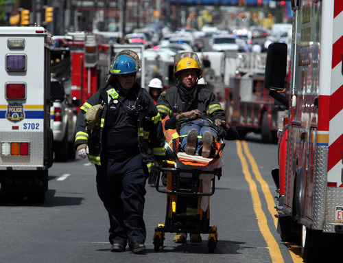 Rescue personnel evacuate an injured person from the scene of a building collapse in downtown Philadelphia Wednesday June 5, 2013.  A four-story building being demolished collapsed Wednesday on the edge of downtown, injuring 12 people and trapping two others, the fire commissioner said.  (AP Photo/Jacqueline Larma)
