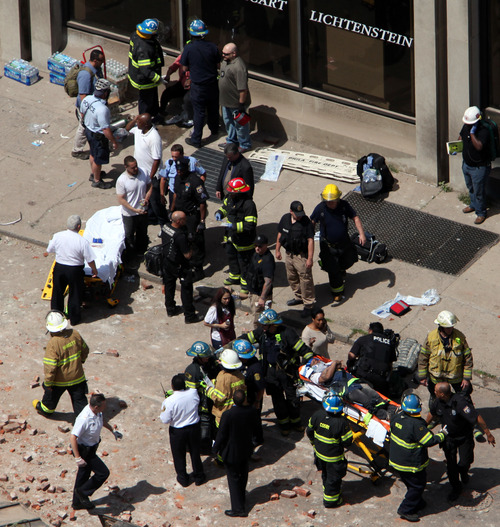 Rescue personnel evacuate an injured person from the scene of a building collapse in downtown Philadelphia, Wednesday, June 5, 2013.  A four-story building being demolished collapsed Wednesday on the edge of downtown, injuring 12 people and trapping two others, the fire commissioner said. Rescue crews were trying to extricate the two people who were trapped, city Fire Commissioner Lloyd Ayers said. The dozen people who were injured were taken to hospitals with minor injuries, according to Ayers. (AP Photo/Jacqueline Larma)