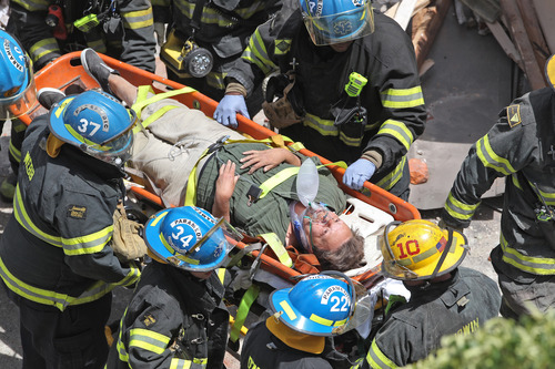 Philadelphia Firefighters carry a survivor from the rubble of a building collapse in downtown Philadelphia Wednesday June 5, 2013.  A four-story building being demolished collapsed Wednesday on the edge of downtown, injuring 12 people and trapping two others, the fire commissioner said. Rescue crews were trying to extricate the two people who were trapped, city Fire Commissioner Lloyd Ayers said. The dozen people who were injured were taken to hospitals with minor injuries, he said. (AP Photo/Philadelphia Inquirer, Michael Bryant)  PHIX OUT; TV OUT; MAGS OUT; NEWARK OUT MAGS OUT;
