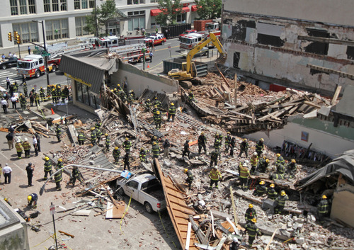 Rescue personnel search the scene of a building collapse in downtown Philadelphia Wednesday June 5, 2013.  A four-story building being demolished collapsed Wednesday on the edge of downtown, injuring 12 people and trapping two others, the fire commissioner said. Rescue crews were trying to extricate the two people who were trapped, city Fire Commissioner Lloyd Ayers said. The dozen people who were injured were taken to hospitals with minor injuries, he said. (AP Photo/Philadelphia Inquirer, Michael Bryant)  PHIX OUT; TV OUT; MAGS OUT; NEWARK OUT MAGS OUT;