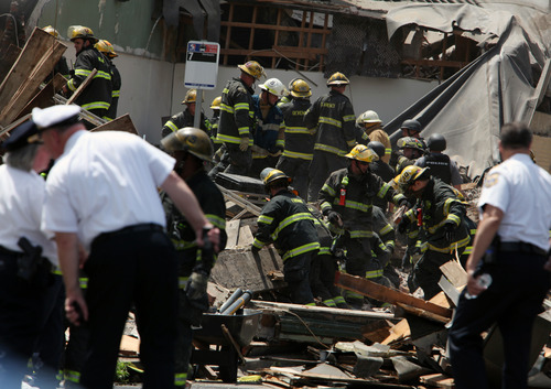 Rescue personnel search the scene of a building collapse in downtown Philadelphia Wednesday June 5, 2013.  A four-story building being demolished collapsed Wednesday on the edge of downtown, injuring 12 people and trapping two others, the fire commissioner said.  (AP Photo/Jacqueline Larma)