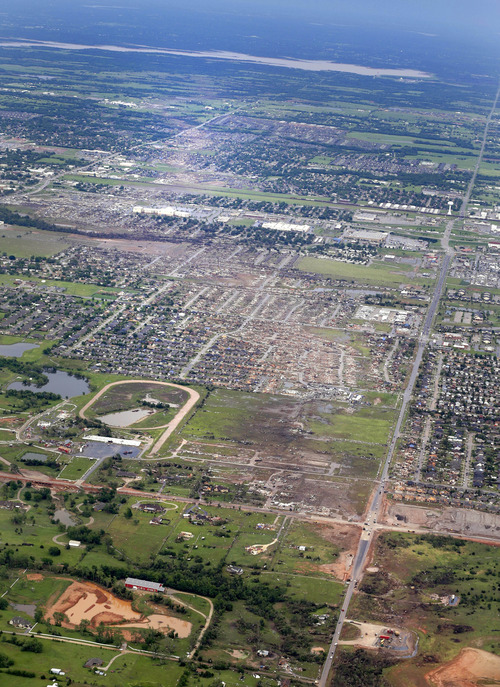 File - This May 21, 2013 file aerial photo shows the remains of houses in Moore, Okla., following a tornado the May 20, 2013 tornado. The Oklahoma City area has seen two of the extremely rare EF5 tornadoes in only 11 days. The tornado that hit El Reno had a record-breaking width of 2.6 miles. The one in Moore, a city about 25 miles away from El Reno, killed 24 people and caused widespread damage. (AP Photo/Kim Johnson Flodin, File)