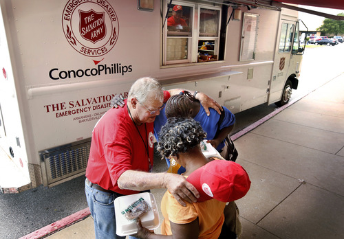 Glen Peterson, a volunteer with a Salvation Army unit in Bartlesville, Okla., prays with two women after they received to-go meals from this Salvation Army canteen parked in front of an Emergency Disaster Services center in south Oklahoma City on Tuesday afternoon, June 4, 2013.  Peterson has been working with displaced victims of late-May tornadoes since arriving in Oklahoma City on May 27. (AP Photo/The Oklahoman, Jim Beckel) LOCAL STATIONS OUT (KFOR, KOCO, KWTV, KOKH, KAUT OUT); LOCAL WEBSITES OUT; LOCAL PRINT OUT (EDMOND SUN OUT, OKLAHOMA GAZETTE OUT) TABLOIDS OUT