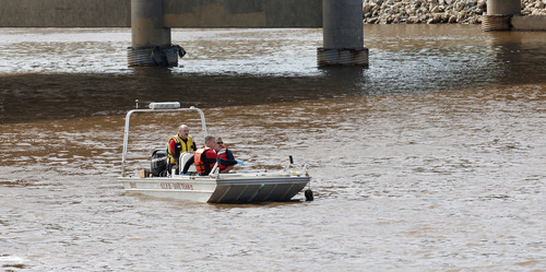 Firemen in the Oklahoma City Fire Department dive team boat head up the Oklahioma River near the north side of the dam across the river, between Walker and Western, while trying to retrieve the body of a storm victim found in Oklahoma City Tuesday, June 4, 2013. (AP Photo/The Oklahoman, Paul B. Southerland)