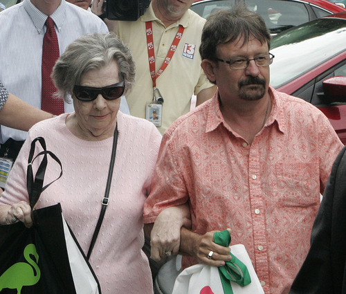 Powerball winner Gloria C. Mackenzie, 84, left, leaves the lottery office escorted by her son, Scott Mackenzie, after claiming a single lump-sum payment of about $370.9 million before taxes on Wednesday, June 5, 2013, in Tallahassee, Fla. Officials say she is the largest sole lottery winner in U.S. history. She did not speak to reporters outside lottery headquarters, leaving in a silver Ford Focus with family members. (AP Photo/Steve Cannon)