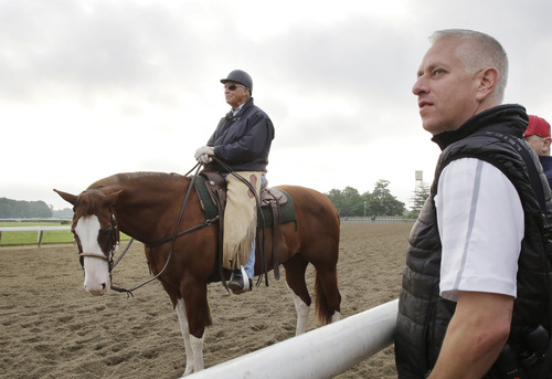 Trainers D. Wayne Lukas, left, and Todd Pletcher watch a morning workout at Belmont Park, Thursday, June 6, 2013 in Elmont, N.Y. Lukas has two entries, and Pletcher five, in Saturday's Belmont Stakes horse race. (AP Photo/Mark Lennihan)