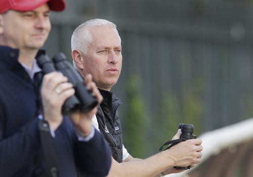 Trainer Todd Pletcher, right, leans on the outside rail to watch his horses gallop on the track at Belmont Park during a morning workout Thursday, June 6, 2013 in Elmont, N.Y. Pletcher has five horses entered in Saturday's Belmont Stakes horse race. Michael McCarthy, left, is an assistant trainer with Pletcher. (AP Photo/Mark Lennihan)