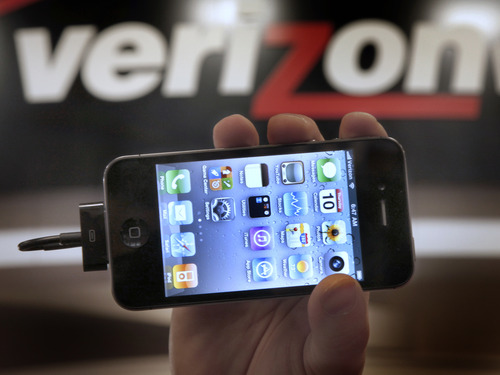 """FILE - In this Feb. 10, 2011 file photo, Chris Cioban, manager of the Verizon store in Beachwood, Ohio, holds up an Apple iPhone 4G. Britain's Guardian newspaper says the National Security Agency is currently collecting the telephone records of millions of U.S. customers of Verizon under a secret court order. The newspaper said Wednesday, June 5, 2013 the order was issued in April and was good until July 19. The newspaper said the order requires Verizon on an """"ongoing, daily basis"""" to give the NSA information on all telephone calls in its systems, both within the U.S. and between the U.S. and other countries.  (AP Photo/Amy Sancetta, File)"""