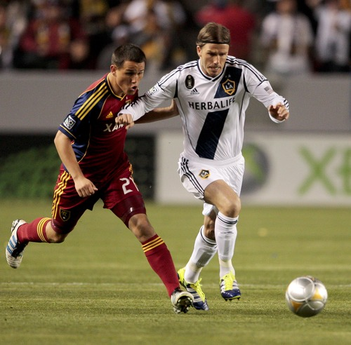 Los Angeles Galaxy midfielder David Beckham, right, shields the ball from Real Salt Lake midfielder Luis Gil during the first half of an MLS soccer match, Saturday, March 10, 2012, in Carson, Calif. (AP Photo/Bret Hartman)