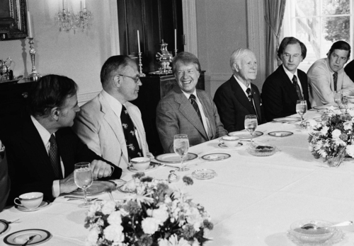 FILE - In this June 2, 1977 file photo, President Jimmy Carter hosts a breakfast in the Family Dining Room of the White House in Washington for House Subcommittee members on Energy and Power.  From left are Rep. John M. Murphy (D-N.Y.), Rep. John Dingell (D-Mich.), President Carter, Rep. Harley Staggers (D-W Va.), Rep. Andrew Maguire (D-N.J.), and Rep. Timothy Wirth (D-Colo.). Fifty seven years ago, Rep. John Dingell, who this week becomes the longest serving member of Congress in history, nearly began his career in tears on the floor of the House. Members were delivering tributes to his father, John Dingell Sr., who had died recently. (AP Photo/Charles Harrity, File)