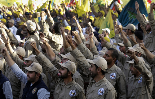 """FILE -- In this Saturday May 25, 2013 file photo, members of the demining unit of Hezbollah, raise up their hands as they shout slogans in support of pro-Hezbollah leader Sheik Hassan Nasrallah, during a rally commemorating """"Liberation Day,"""" which marks the withdrawal of the Israeli army from southern Lebanon in 2000, in Mashghara village, Bekaa valley, Lebanon. Syria's civil war has morphed into a proxy fight in which Shiite Iran has strongly backed Assad, while Sunni Arab nations have backed rebels. Many Sunni hard-liners around the Mideast have taken Hezbollah's intervention in Syria almost as a declaration of war by Shiites against Sunnis. (AP Photo/Hussein Malla, File)"""