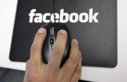 FILE - In this Tuesday, Dec. 13, 2011, file photo, a Facebook User Operations Safety Team worker looks at reviews at Facebook headquarters in Menlo Park, Calif. The Washington Post and The Guardian reported Thursday, June 6, 2013, the existence of a program used by the NSA and FBI that scours the nation's main Internet companies, extracting audio, video, photographs, emails, documents and connection logs to help analysts track a person's movements and contacts. (AP Photo/Paul Sakuma, File)