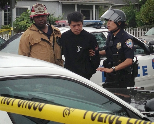 Los Angeles Police officers detain an unidentified man near a shooting at Santa Monica College, Friday, June 7, 2013, in Santa Monica, Calif.  Two people were found dead in a burned home near the college, where someone sprayed a street corner with gunfire, wounding at least four people, authorities said. (AP Photo/Tami Abdollah)