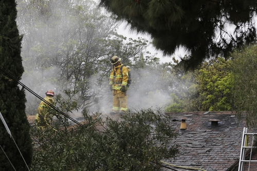 Firefighters work at a burning home about a mile northeast of Santa Monica College in Santa Monica, Calif. Friday, June 7, 2013. Two people were found dead in the burned home where someone sprayed a street corner with gunfire, wounding at least three people, authorities said. (AP Photo/Reed Saxon)