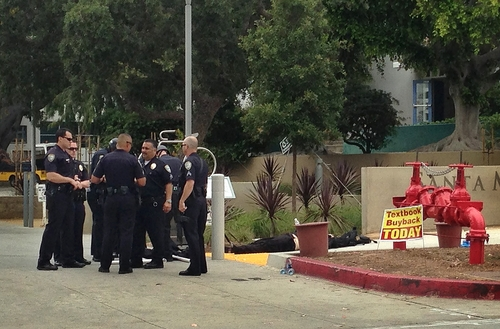 Police officers stand next to a body near an entrance to Santa Monica College, Friday, June 7, 2013, in Santa Monica, Calif., following a shooting incident in the area.  Two people were found dead in a burned home near the college, where someone sprayed a street corner with gunfire, authorities said. (AP Photo/Tami Abdollah)