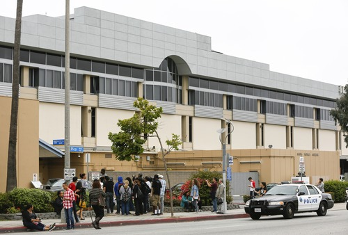 Students stand outside the north side of  Santa Monica College campus in Santa Monica, Calif. Friday, June 7, 2013. Two people were found dead Friday in a burned home near college, where someone sprayed a street corner with gunfire, wounding at least three people, authorities said. (AP Photo/Damian Dovarganes)