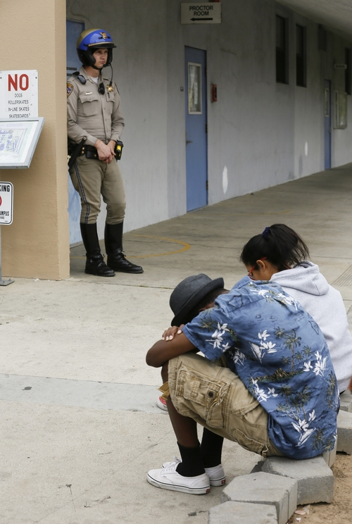 A California Highway Patrol officer stands guard as students students wait outside the north side of the lock down Santa Monica College campus in Santa Monica, Calif. Friday, June 7, 2013. Two people were found dead Friday in a burned home near the school, where someone sprayed a street corner with gunfire, wounding at least three people, authorities said. (AP Photo/Damian Dovarganes)