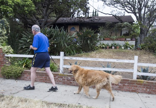 Mark Adams, 62, walks his dog, Gunnar, in Santa Monica, Calif. on Saturday, June 8, 2013 past the home that burned at the scene of a shooting on Friday. The gunman, dressed all in black and carrying a semi-automatic rifle, walked through the Santa Monica College campus after killing his father, brother at the home and another man near the school, authorities said. He would kill a woman outside the library moments later, before dying from police gunfire. (AP Photo/Ringo H.W. Chiu)