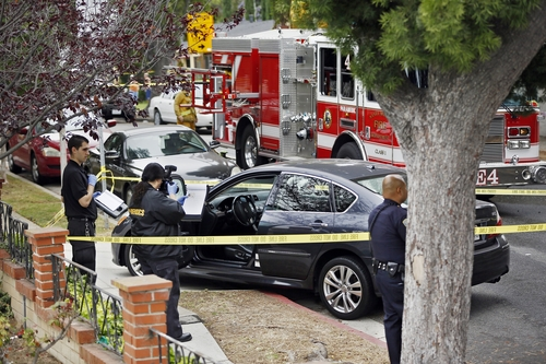 Forensic investigators photograph a car with bullet holes across a home that caught fire in Santa Monica, Calif. Friday, June 7, 2013. Two people were found dead Friday in a burned home near the school, where someone sprayed a street corner with gunfire, wounding at least three people, authorities said. (AP Photo/Damian Dovarganes)