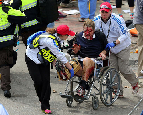 (AP Photo/The Boston Globe, David L. Ryan) Medical workers aid an injured man at the 2013 Boston Marathon after an explosion on April 15 caused by two bombs.