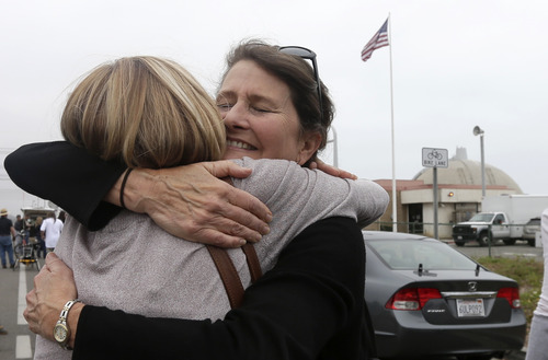 Laurie Headrick, right, hugs Chrystal Coleman, left, near the gate to the San Onofre Nuclear Power plant, right, as they wait for the beginning of a news conference held by opponents of the plant Friday, June 7, 2013, in San Onofre, Calif. The troubled power plant on the California coast is closing after an epic 16-month battle over whether the twin reactors could be safely restarted with millions of people living nearby, officials announced Friday. (AP Photo/Gregory Bull)