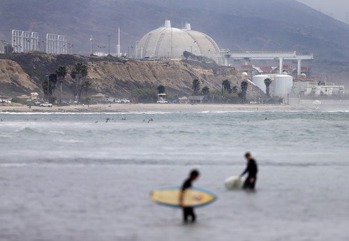Surfers pass in front of the San Onofre nuclear power plant Friday, June 7, 2013, in San Onofre, Calif. The troubled power plant on the California coast is closing after an epic 16-month battle over whether the twin reactors could be safely restarted with millions of people living nearby, officials announced Friday. (AP Photo/Gregory Bull)
