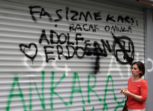 A woman walks past graffiti painted by protesters including a crossed out swastika and the term 'Adolf Erdogan' in the city's Kugulu Park, where a group continue reading books, dancing or playing musical instruments in Ankara, Turkey, Saturday, June 8, 2013.  A senior European Union official, the EU enlargement commissioner Stefan Fule, on Friday criticized Turkish police's harsh crackdown on protesters in the last week, asked that abusers be investigated and punished and told an audience that included Turkish prime minister Recep Tayyip Erdogan, that as a EU-candidate country, Turkey should aspire to the highest standards of democracy.(AP Photo/Burhan Ozbilici)