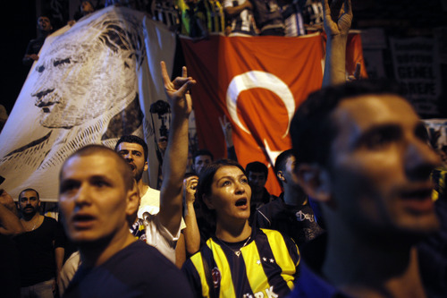 Protesters sing Turkey's national anthem  during a protest at Taksim square in Istanbul Saturday, June 8 2013. Turkey's Prime Minister Recep Tayyip Erdogan convened his party leadership Saturday as anti-government protests entered their ninth day, with thousands of people still occupying Istanbul's central Taksim Square and the main Kizilay Square in Ankara.(AP Photo/Kostas Tsironis)
