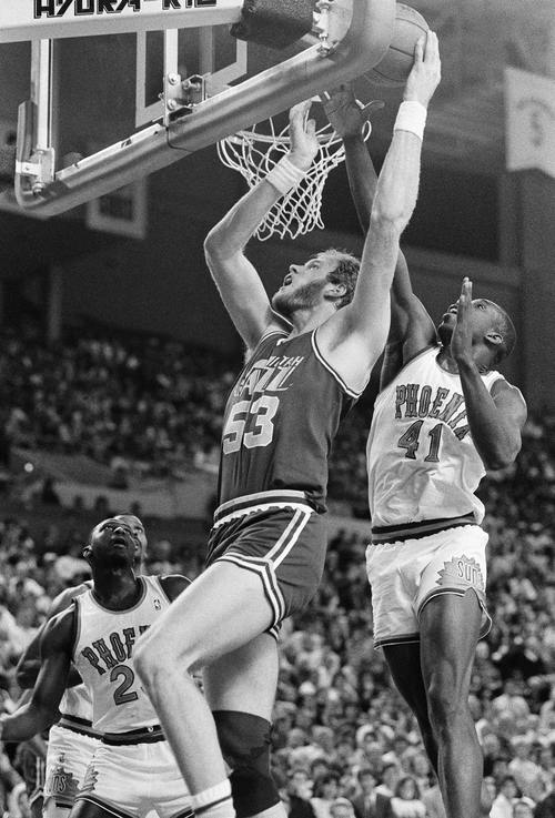 Utah Jazz Mark Eaton goes up and over Phoenix Suns center Mark West while shooting from behind the basket during the game in Phoenix February 7, 1989. (AP Photo/Chad Surmick)